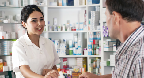 Female pharmacist dispensing a prescription to a male client